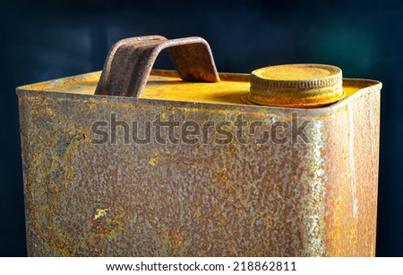 Old rusty tin gallon gas can with cap on black background - stock photo