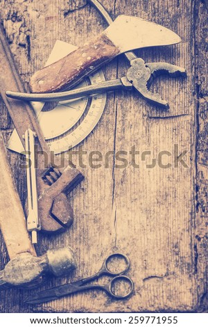 Old rusty tools, scissors, hammer on old wooden table background - stock photo
