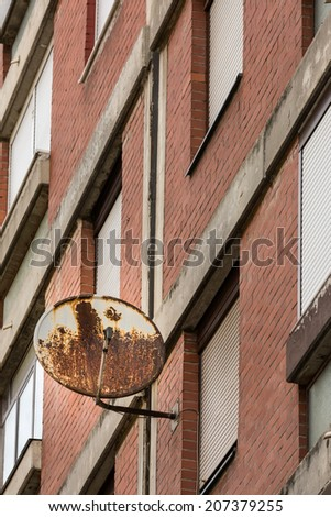 Old rusty TV receiver satellite dish installed on residential building window, symbol of old technology, as opposed to the modern wired and optical cable TV systems - stock photo