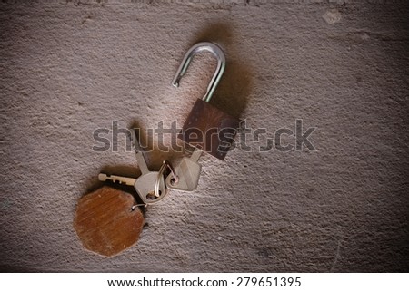 old rusty vintage iron keys on cement background. - stock photo