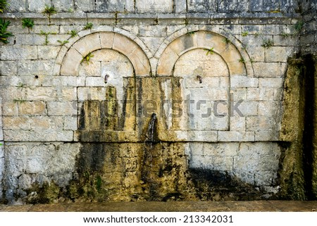 Old rusty water tap in village - stock photo