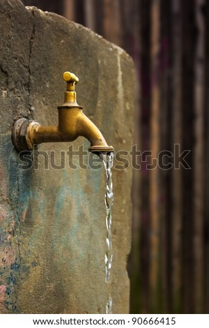 Old rusty water tap on cracked concrete wall - stock photo