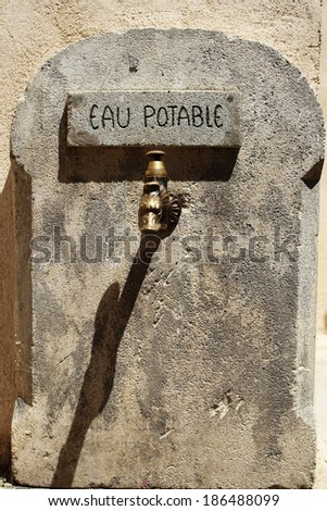 Old rusty water tap  on cracked stone wall  in France - stock photo