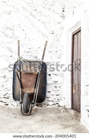 Old rusty wheelbarrow - stock photo