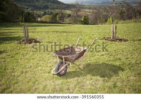 Old rusty wheelbarrow cart in the garden - stock photo
