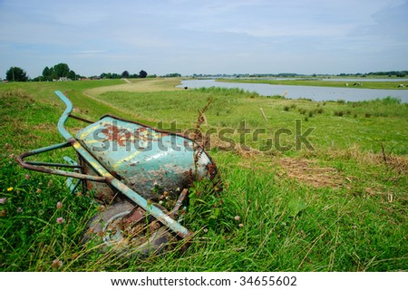 Old rusty wheelbarrow lying in a green meadow