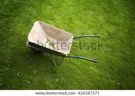 Old rusty wheelbarrow on a green grass field background. Top view perspective used. - stock photo