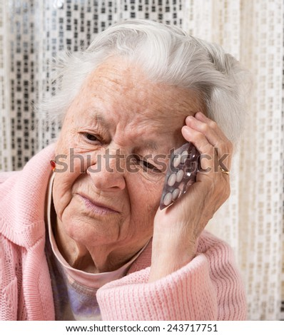 Old sad woman holding pills at home