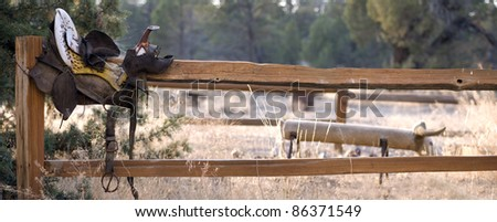 Old saddle on split rail fence with roping dummy in the background.  2 image stitch. - stock photo