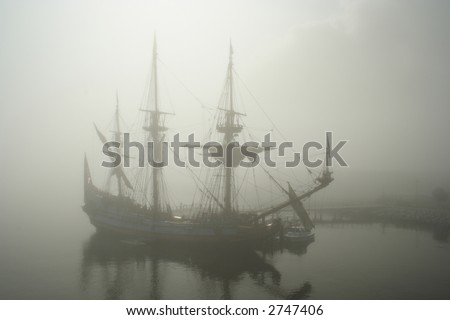 Old sail ship (Pirate?) in the fog early morning - stock photo