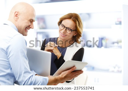 Old sales man consulting with middle age business woman while sitting at office. Teamwork at office.  - stock photo