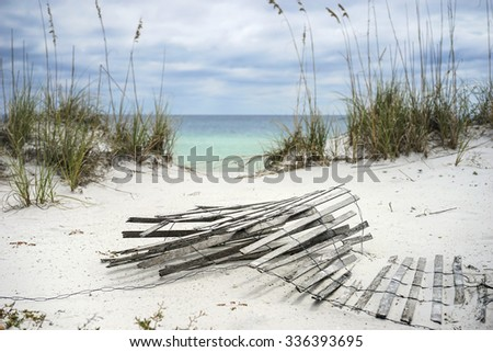 Old sand fence lying on the beach in winter in Florida. - stock photo