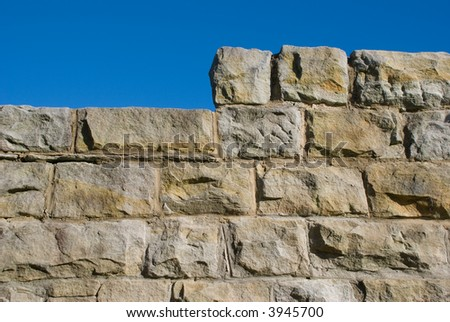 Old sandstone wall with stepped or raised section and blue sky - stock photo