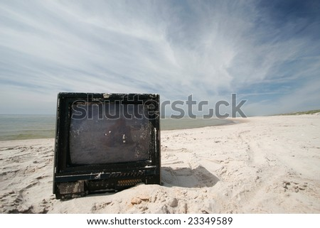 Old sandy tv on the beach - stock photo