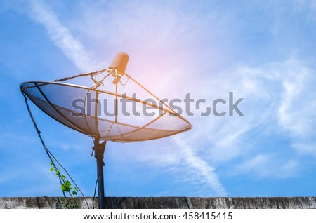 Old satellite dish and green leaf plants on top roof with blue sky and white cloud background. Copy space of communication technology concept. Vintage tone filter color style. - stock photo