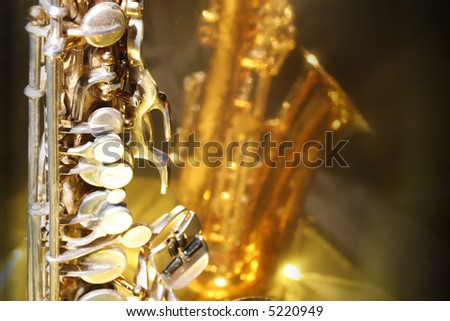 Old saxophone against a bright golden reflective surface with copy space - stock photo