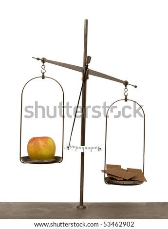 Old scales with apple and chocolate isolated on white background, showing that the apple is the lighter choice - stock photo