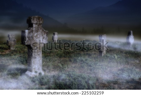 Old scary graveyard hidden in mist with mountains in the background - stock photo