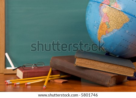 Old school books on a desk with a globe in front of a green chalkboard - stock photo