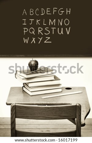 Old school desk with a stack of books and apple/ Sepia tone - stock photo