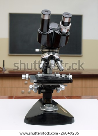 Old school microscope in classroom with blackboard in the background - stock photo
