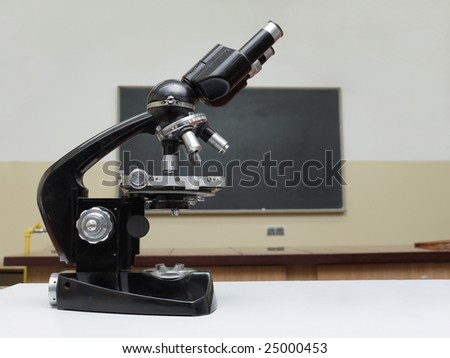Old school microscope in classroom with blackbroard in the background - stock photo