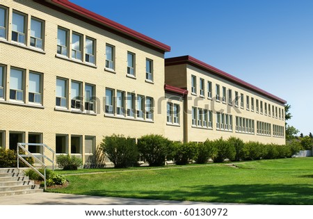 Old school or hospital wing made of yellow bricks, with green grass and blue sky. - stock photo