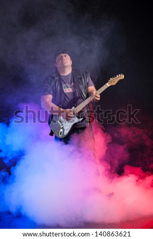 old school rock musician is playing electrical guitar. Shot in a studio. - stock photo