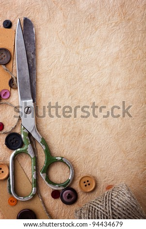 Old scissors and buttons on the paper texture - stock photo