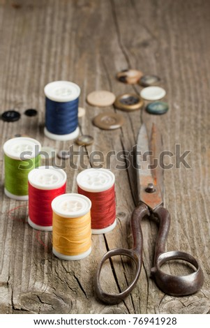 Old scissors, cottons and buttons on wooden desk