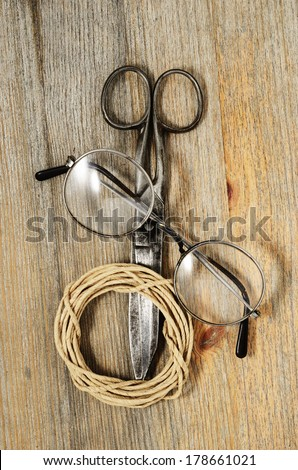 old scissors, glasses and hank of packthread over wooden texture - stock photo