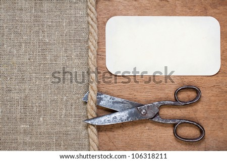 Old scissors on canvas and wood textured background with paper frame