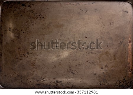 Old, scratched, and rusted oven baking sheet grunge background.