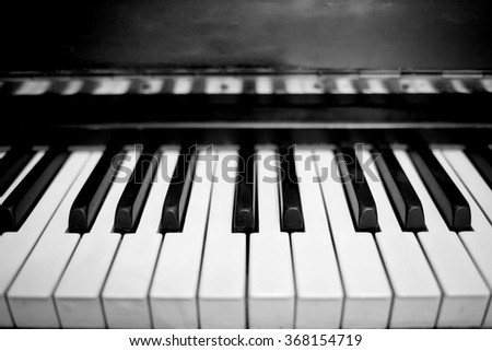 Old scratched dusty piano. Black and white image with selective focus - stock photo