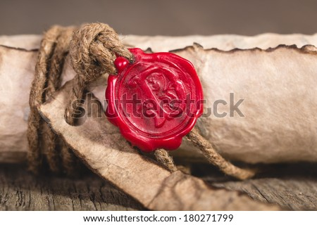 Old scroll paper on wooden background. Close up of wax seal. - stock photo