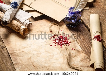 Old scrolls, sealing wax and blu ink on wooden table - stock photo