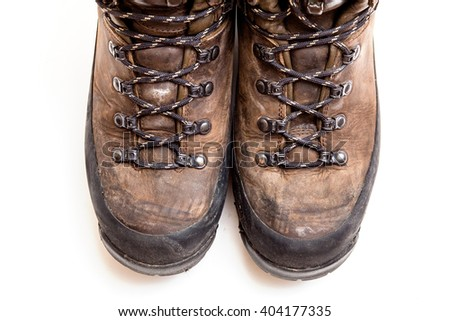 Old scuffed hiking boots isolated on white background - stock photo