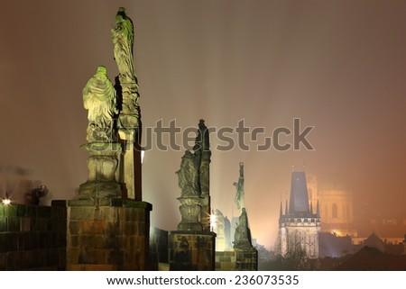 Old sculptures and distant Gothic towers along the Charles bridge illuminated by night, Prague, Czech Republic - stock photo