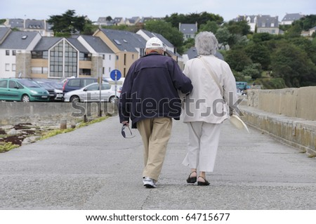 Old senior couple walking together holding their hands - stock photo