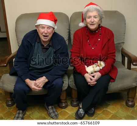 Old senior couple with santa hats celebrating christmas - stock photo