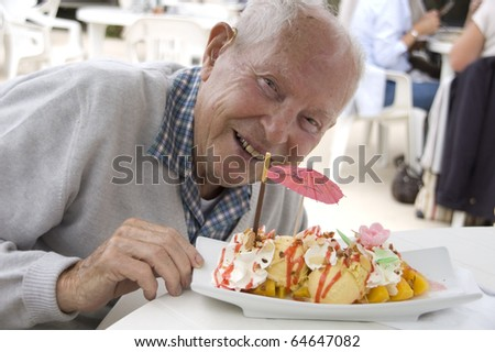 Old senior man enjoying his sweet ice cream sundae - stock photo