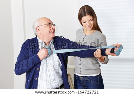 Old senior man exercising at rehabilitation in physiotherapy - stock photo