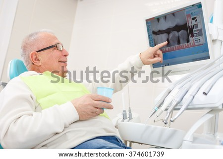 Old senior man on a dental clinic. Sitting in a chair and look X-Ray on computer - stock photo