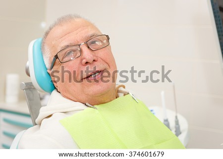 Old senior man with glasses sitting in a dental chair in a dentist's office. - stock photo
