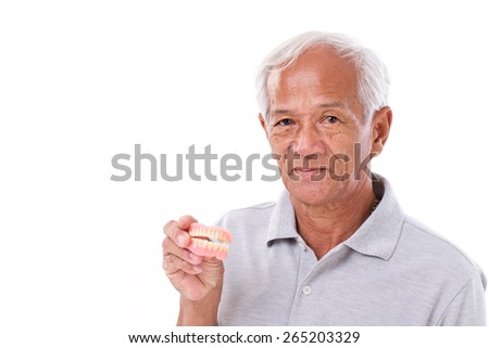 old senior man with hand holding denture - stock photo