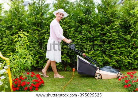 Old senior woman gardener 65 years old in hat, mowing grass with an electric mower in garden, summer morning
