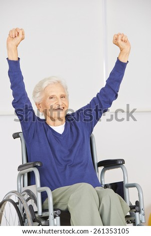Old senior woman in wheelchair cheering with her arms up - stock photo
