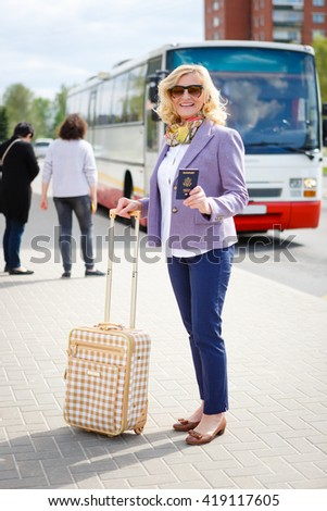 Old senior woman tourist holding a passport and suitcase in a bus station in Europe city - stock photo