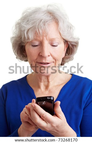 Old senior woman using the internet with her mobile phone - stock photo