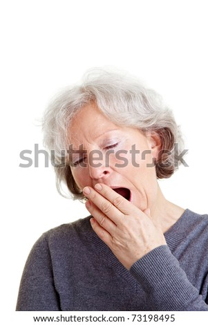Old senior woman yawning with hand in front of her mouth - stock photo